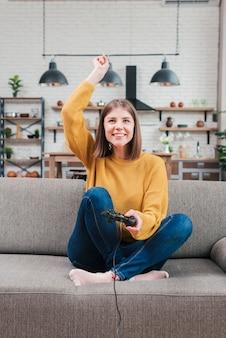 Mujer joven sonriente que se sienta en el sofá que anima mientras que juega al videojuego