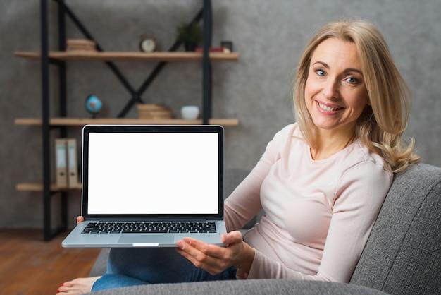 Mujer joven sonriente que se sienta en el sofá que muestra su exhibición del ordenador portátil