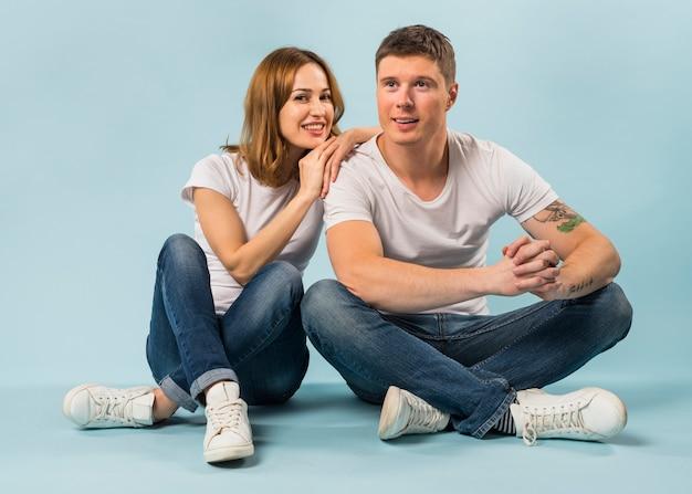Mujer joven sonriente que sienta a su novio contra fondo azul
