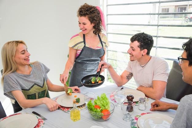 Mujer joven sonriente que sirve verduras cocinadas a sus amigos en la mesa de comedor