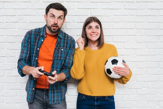 Mujer joven sonriente que sostiene el balón de fútbol en la mano que anima a su novio que juega al videojuego
