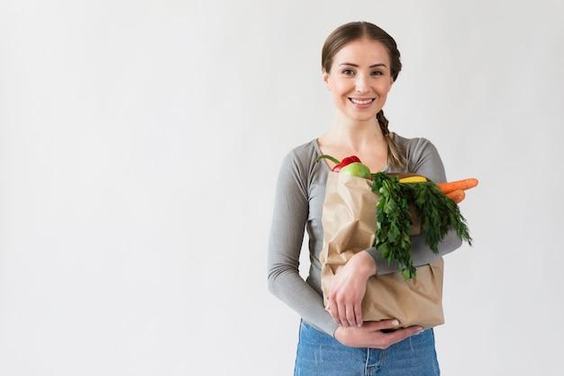 Mujer joven sonriente que sostiene la bolsa de papel con las verduras