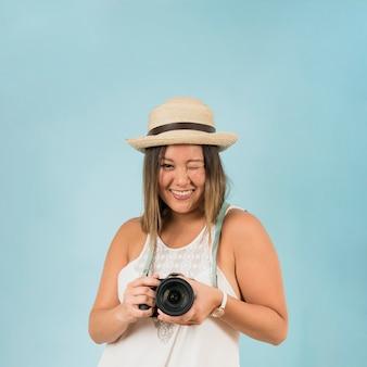 Mujer joven sonriente que sostiene la cámara en la mano que guiña contra el contexto azul