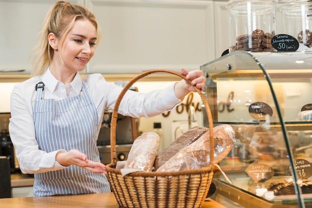 Mujer joven sonriente que sostiene la cesta de baguette en la cafetería