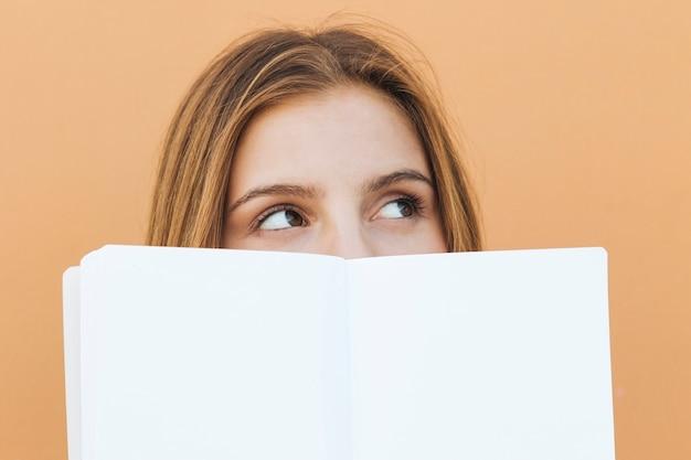 Mujer joven sonriente que sostiene el libro blanco en su mano que mira la cámara