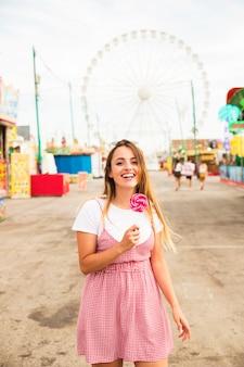 Mujer joven sonriente que sostiene la piruleta en la mano que se coloca en el parque de atracciones