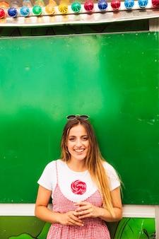Mujer joven sonriente que sostiene la piruleta roja que se coloca delante de la pared verde