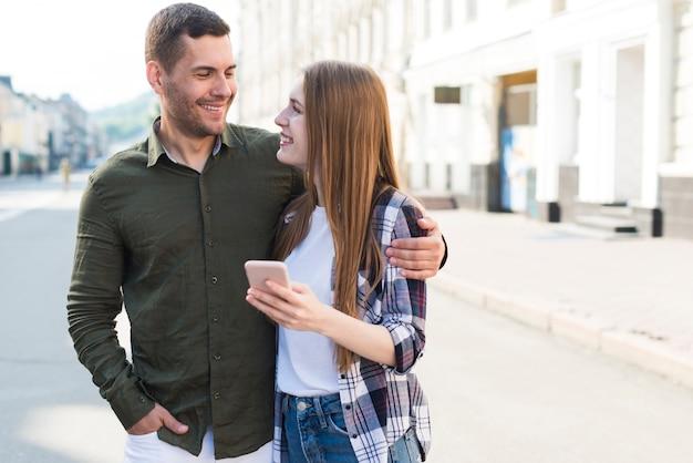 Mujer joven sonriente que sostiene smartphone y que mira a su novio en la calle