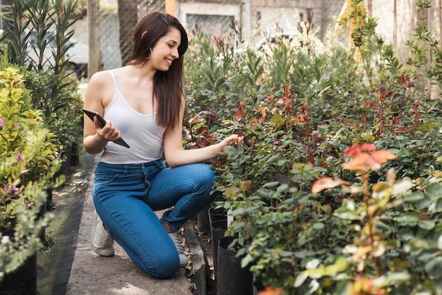 Mujer joven sonriente que sostiene la tableta digital disponible que cultiva un huerto en el invernadero