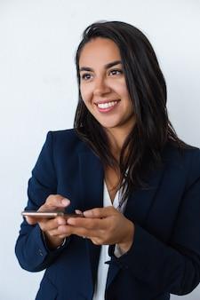 Mujer joven sonriente que sostiene el teléfono móvil