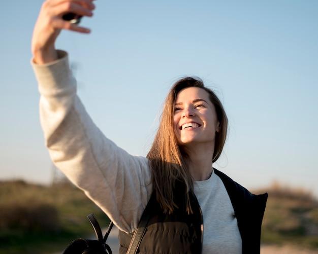 Mujer joven sonriente que toma una foto del uno mismo