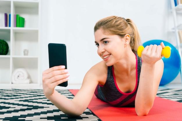 Mujer joven sonriente que toma el selfie en el teléfono móvil mientras que hace ejercicio con pesa de gimnasia amarilla