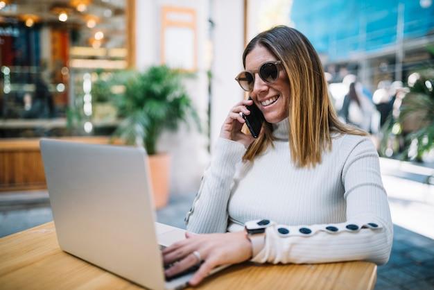 Mujer joven sonriente que usa el ordenador portátil y el smartphone en la tabla en café de la calle