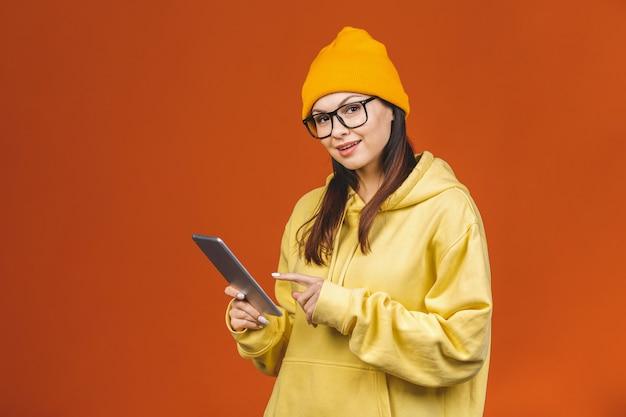 Mujer joven sonriente que usa la tableta aislada en fondo anaranjado.