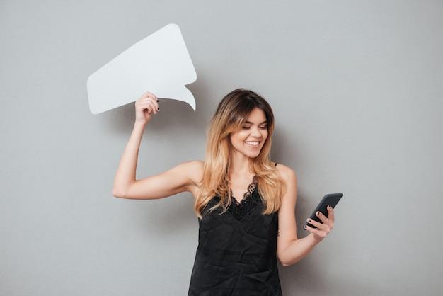 Mujer joven sonriente que usa el teléfono móvil y sosteniendo el bocadillo de diálogo