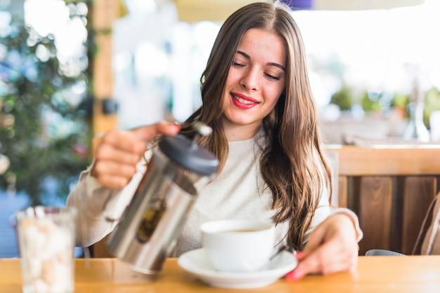 Mujer joven sonriente que vierte té de hierbas en la taza