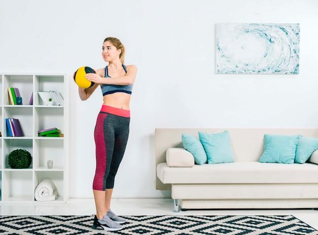 Mujer joven sonriente en ropa deportiva que ejercita con la bola médica en la sala de estar