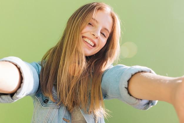Mujer joven sonriente rubia en la luz del sol que toma el selfie contra fondo verde