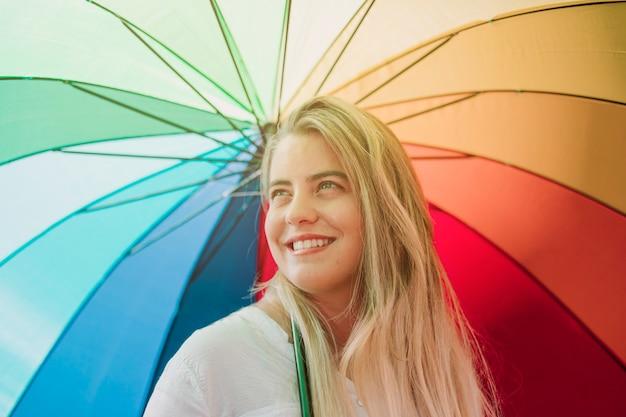 Mujer joven sonriente rubia que sostiene el paraguas del arco iris