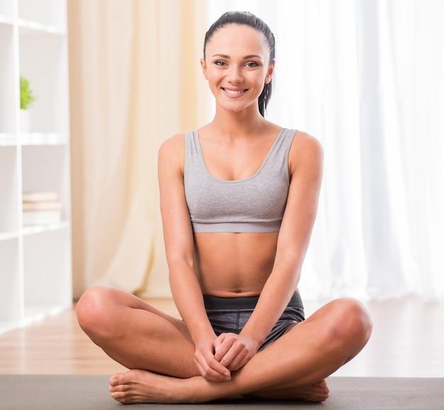 La mujer joven sonriente está sentada en la estera en casa.