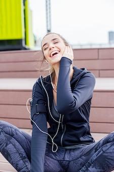Mujer joven sonriente con smartphone y auriculares escuchando música