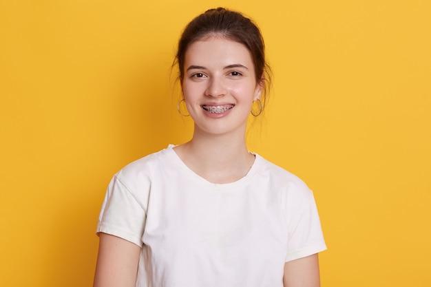 Mujer joven sonriente con soportes y aretes redondeados posando contra la pared amarilla
