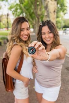 Mujer joven sonriente con su amigo femenino que muestra el compás