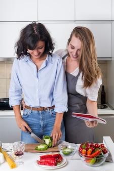 Mujer joven sonriente y su amigo que preparan la comida en la cocina