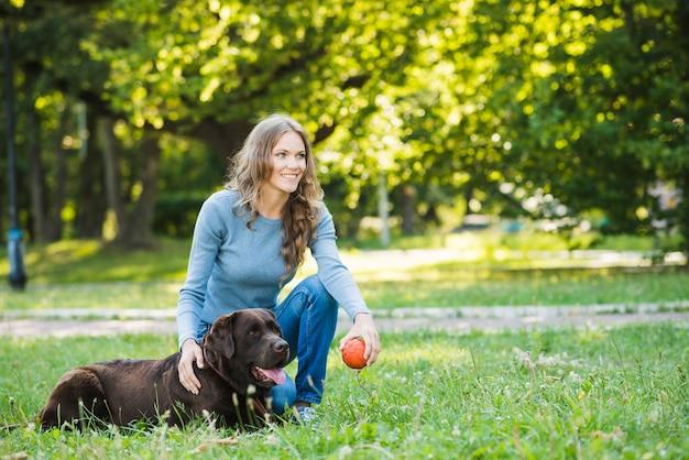 Mujer joven sonriente con su perro en jardín
