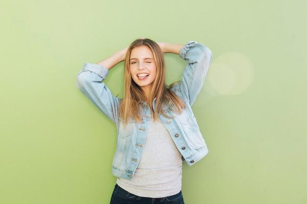 Mujer joven sonriente con sus manos detrás de la cabeza que guiña contra el contexto verde