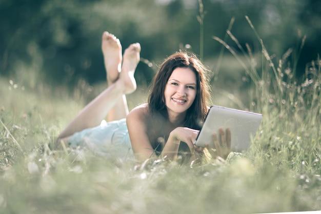 Mujer joven sonriente con tableta digital sobre fondo de pradera de verano.