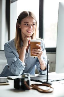 La mujer joven sonriente trabaja en oficina usando la computadora que bebe el café.