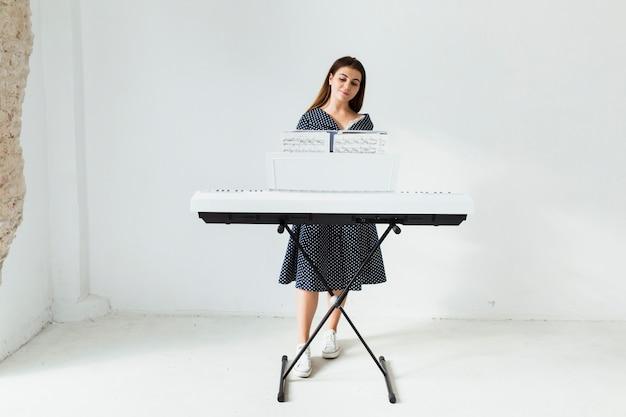 Mujer joven sonriente en vestido de polca tocando el piano