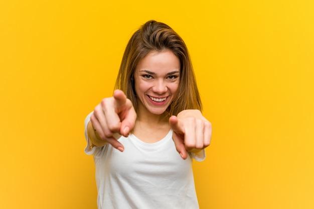 Mujer joven sonrisas alegres apuntando al frente