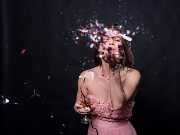 Mujer joven, soplar, confeti