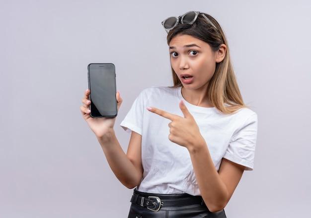 Una mujer joven sorprendente en camiseta blanca con gafas de sol mostrando teléfono móvil