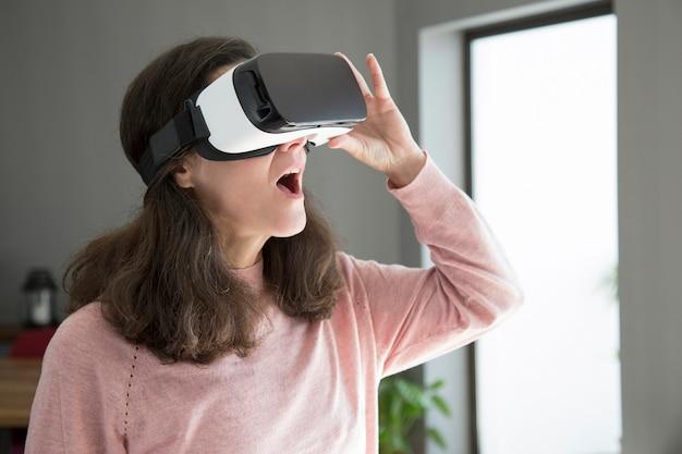 Mujer joven sorprendida con la boca abierta viendo video