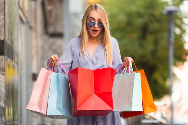 Mujer joven sorprendida por bolsas de compras