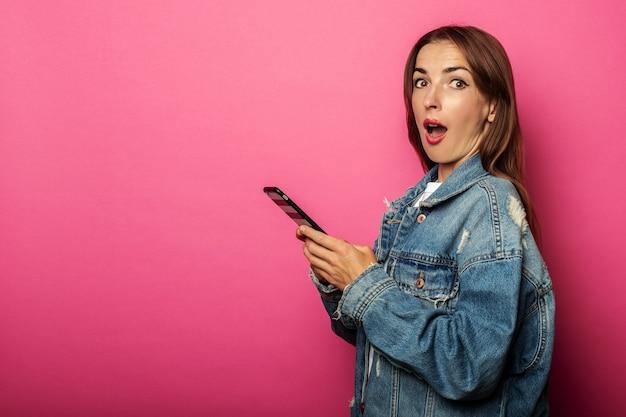Mujer joven sorprendida en chaqueta de mezclilla con teléfono