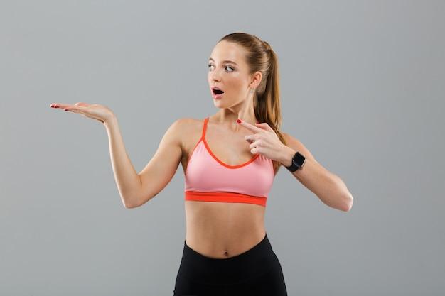 Mujer joven sorprendida de los deportes que señala al copyspace.