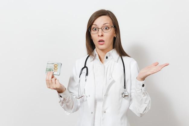 Mujer joven sorprendida del doctor con el estetoscopio, vidrios aislados en el fondo blanco. doctora en bata médica con billetes de dinero en efectivo, paquete de dólares. personal sanitario, concepto de medicina.