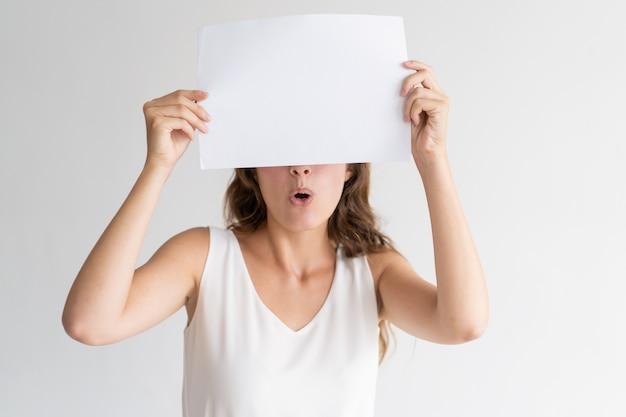 Mujer joven sorprendida escondida detrás de una hoja de papel en blanco