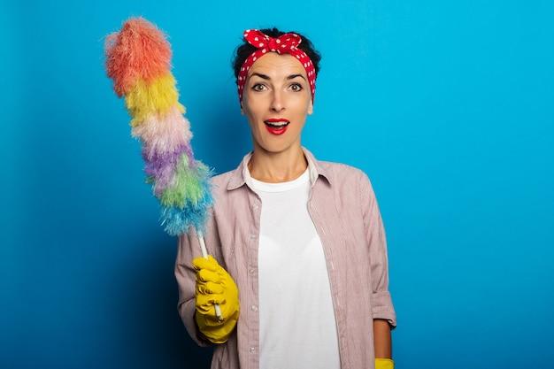 Mujer joven sorprendida en guantes con cepillo para polvo sobre superficie azul