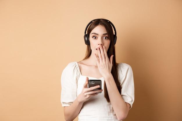 Mujer joven sorprendida jadeando y cubriendo la boca con la mano, usando auriculares inalámbricos para escuchar podcast o música, sosteniendo el teléfono móvil, fondo beige.