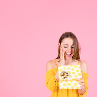 Mujer joven sorprendida que abre la caja amarilla del presente del lunar con el arco de oro