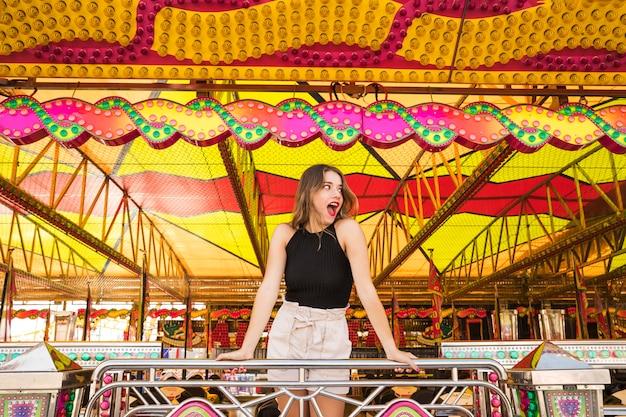 Mujer joven sorprendida que se coloca debajo de la tienda adornada en el parque de atracciones