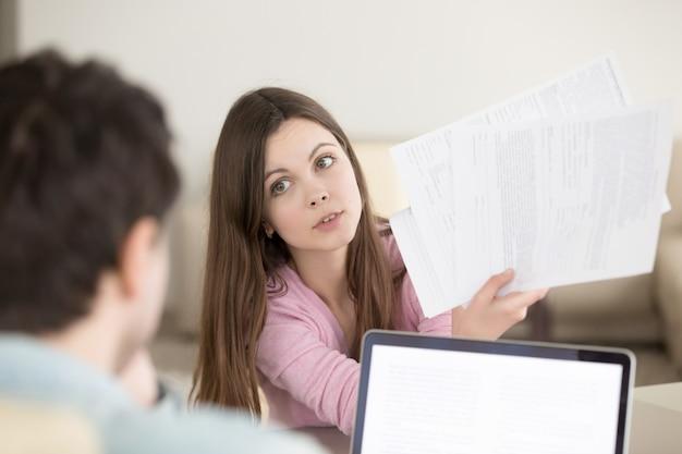 Mujer joven sorprendida que muestra los papeles al hombre con loo que pregunta