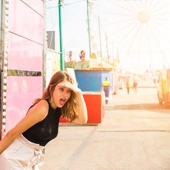 Mujer joven sorprendida que se protege sus ojos en el parque de atracciones