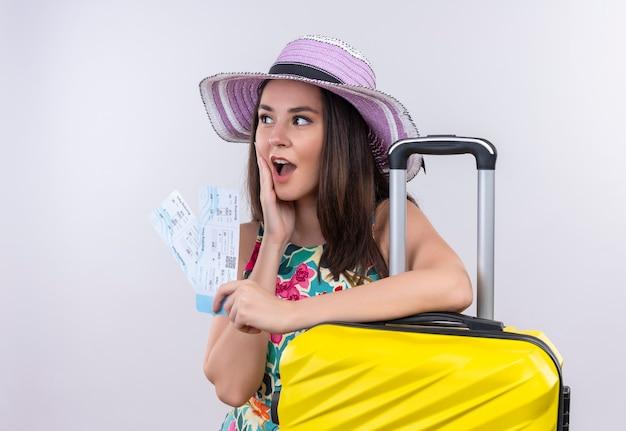 Mujer joven sorprendida que sostiene los billetes de avión y la maleta en la pared blanca aislada