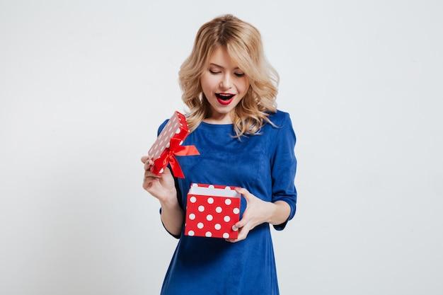 Mujer joven sorprendida que sostiene la caja de regalo sobre la pared blanca